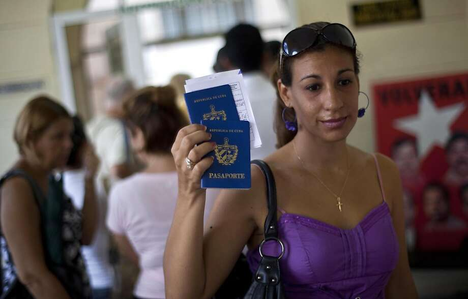 A Cuban woman picks up a passport for herself and her son at an immigration office in Havana. Cuba announced Tuesday that exit visas will no longer be required to travel abroad. Photo: Ramon Espinosa, Associated Press