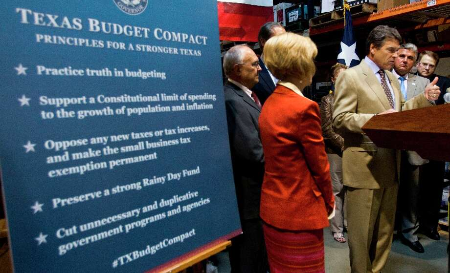 Gov. Rick Perry, right, makes a statement during a news conference discussing the need for stricter spending limits in Texas on Tuesday, Sept. 25, 2012, in Houston. Photo: Brett Coomer, Houston Chronicle / © 2012 Houston Chronicle