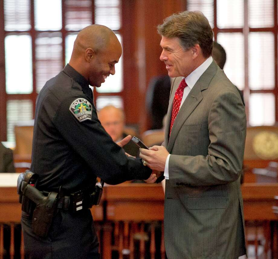 Texas Gov. Rick Perry presents seriously injured Austin Police officer Frank Wilson V. with his medal after Perry gave remarks and presented the 2012 Star of Texas Awards, during a ceremony in the House Chambers in Austin, Texas, Friday morning, Sept. 14, 2012. (AP Photo/Statesman.com, Ralph Barrera)  MAGS OUT; NO SALES; INTERNET AND TV MUST CREDIT PHOTOGRAPHER AND STATESMAN.COM Photo: Ralph Barrera, Associated Press / American-Statesman