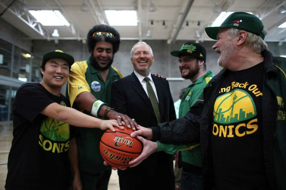 Supporters hold a basketball with Seattle Mayor Mike McGinn after he signed a law approving financing of a proposed NBA and NHL arena in Seattle's Sodo neighborhood. Photo: JOSHUA TRUJILLO / SEATTLEPI.COM