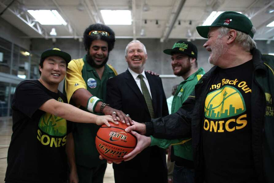 Supporters hold a basketball with Seattle Mayor Mike McGinn after he signed a law approving financin
