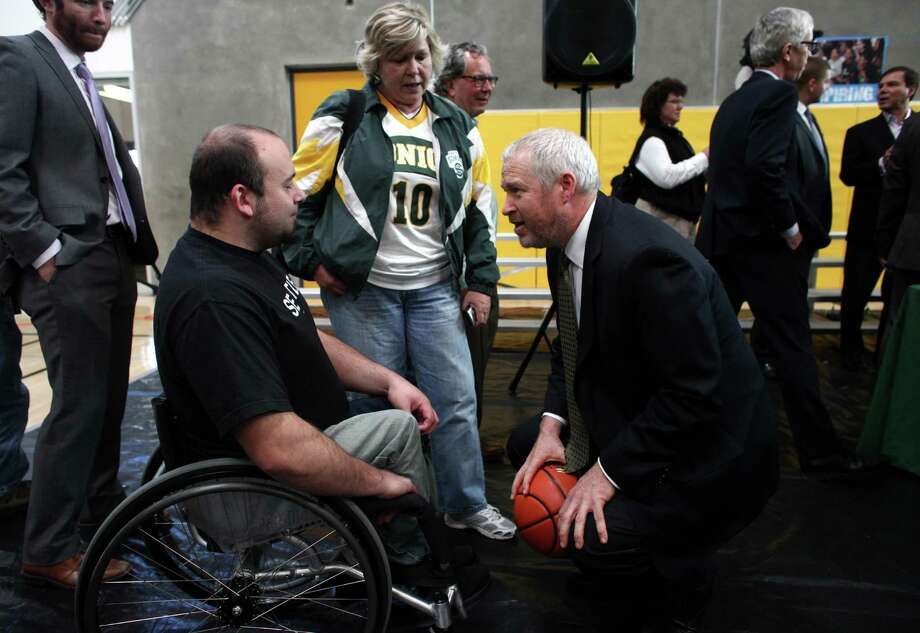 Seattle Mayor Mike McGinn speaks to Matthew Gee of the Wheel Chair Sonics of the Seattle Adaptive Sports league after the mayor signed a law approving financing of a proposed NBA and NHL arena in Seattle. Photo: JOSHUA TRUJILLO / SEATTLEPI.COM