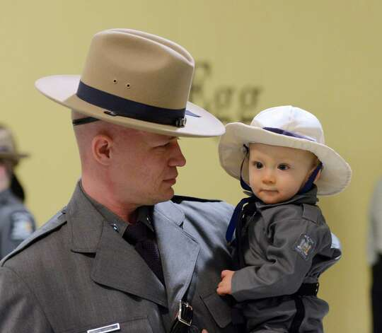 Trooper graduate, former Albany Police Officer Christopher Orth hold 11 month old son Tyson Orth who is dressed in a traditional trooper uniform made by his 92 year old great grandmother Phoebe Lewinski at the State Police Graduation at the Empire State Plaza Convention Center in Albany, N.Y. Oct 16, 2012.       (Skip Dickstein/Times Union) Photo: Skip Dickstein / 00019675A
