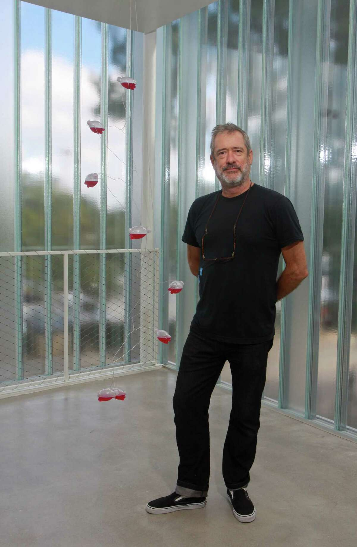 """Artist Tony Feher took wire hangers, plastic bottles with plastic caps, ink, water and twine to create his 2007 mobile """"(Pinks)."""" It is on exhibit at the Blaffer Gallery at the University of Houston."""