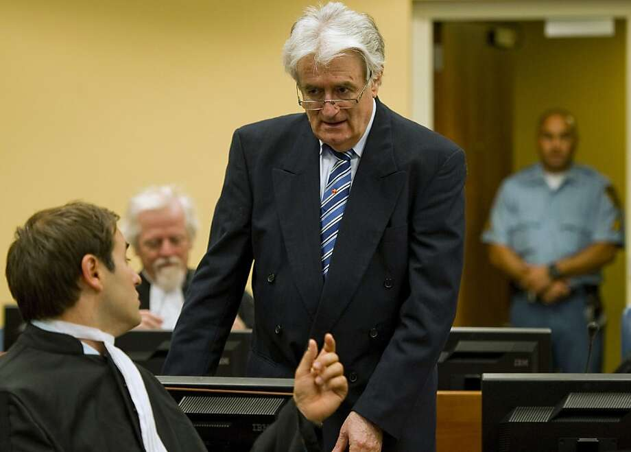 Suspected war criminal and former Bosnian Serb leader Radovan Karadzic, standing, talks to Marko Sladojevic, left, a member of his legal team as he takes his seat on the defense bench at the U.N. war crimes tribunal in The Hague, Netherlands, Tuesday, Oct. 16, 2012. (AP Photo/Robin van Lonkhuijsen, Pool) Photo: Robin Van Lonkhuijsen, Associated Press