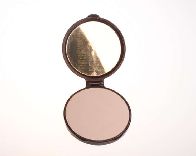 A lady's makeup compact containing a code in the mirror. By tilting the mirror at the correct angle,