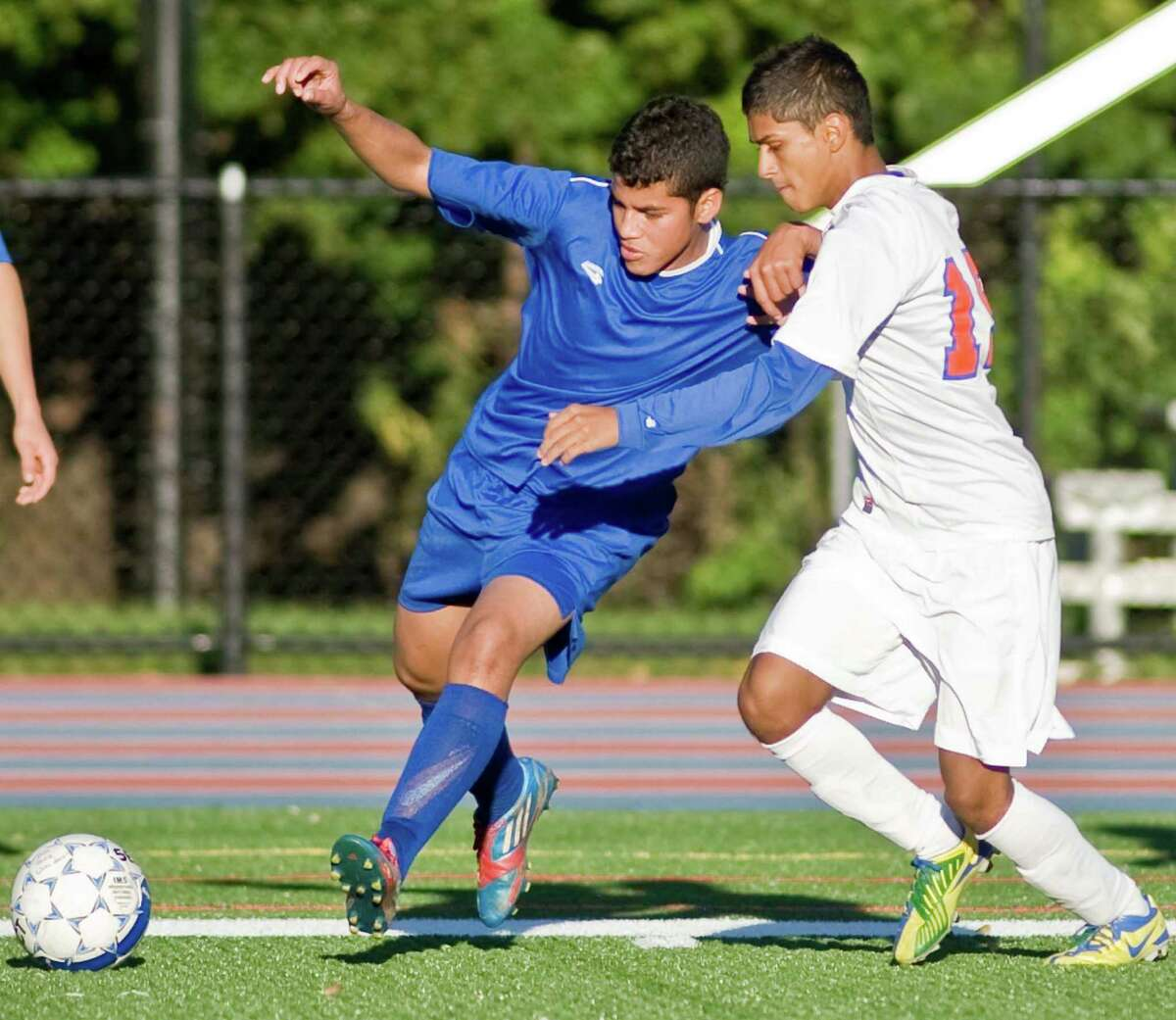 Harding High School's Arturo Rocha and Danbury High School's Richard Sant'Anna make contact while chasing the ball in a game at Danbury. Tuesday, Oct. 16, 2012