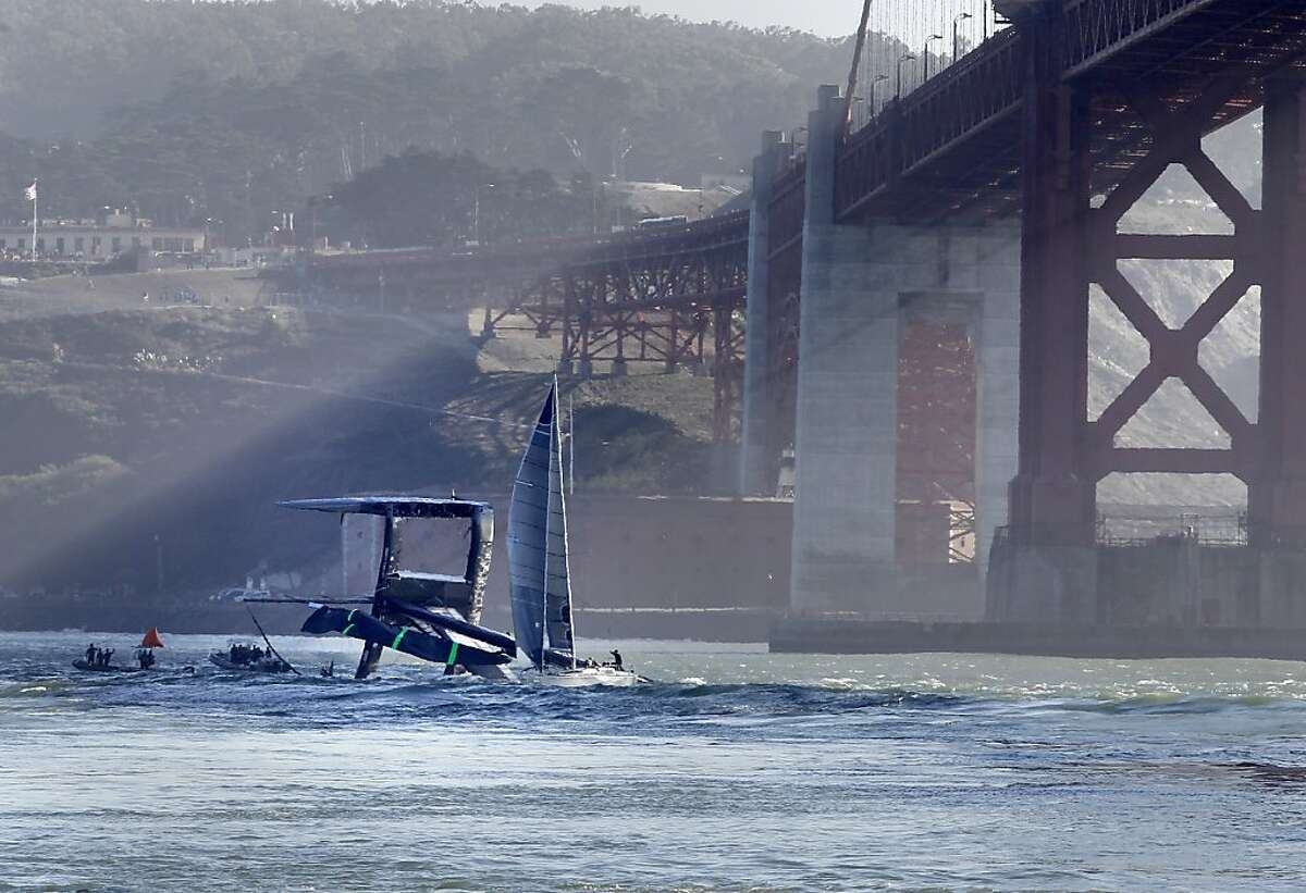 Crews try to tow Oracle's AC72 back to San Francisco after the yacht flipped during training. The wing - the device at the center of the boat that catches the wind - was badly damaged.