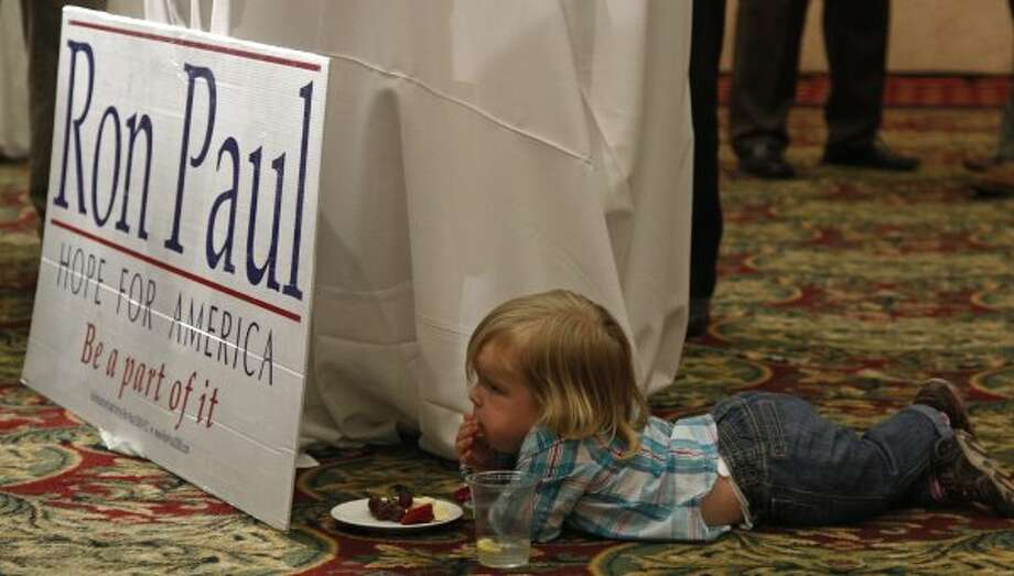 Eisley Collins, 2, snacks next to a Ron Paul sign at a Republican watch party in Oklahoma City, Tuesday, March 6, 2012. (Sue Ogrocki / The Associated Press)
