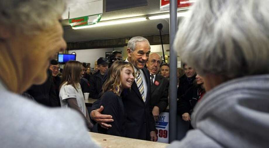 Ron Paul poses for a photograph while campaigning at Sandy's Variety Store in Manchester, N.H., Tuesday Dec. 20, 2011. (Charles Krupa / The Associated Press)