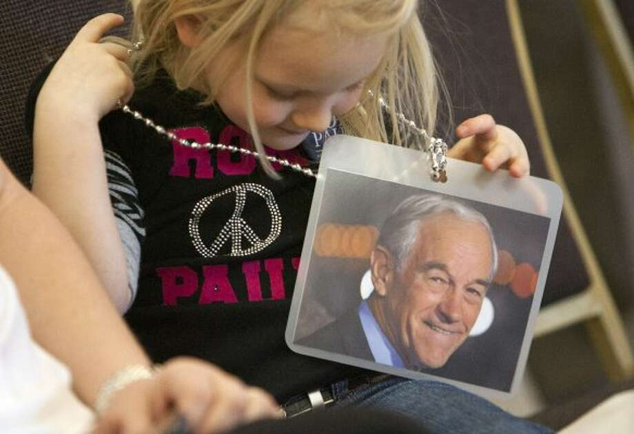 Sydney Walker, 4, holds a picture of Republican presidential candidate Ron Paul before he spoke at a rally on Tuesday, March 6, 2012 in Nampa, Idaho. (Katherine Jones / The Associated Press)