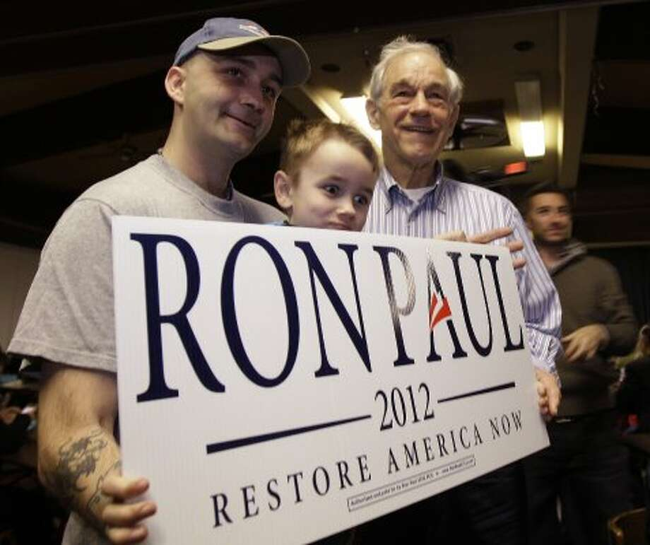 Ron Paul poses for a photo with supporter David Larsen and his step-son Zac, during a Washington state caucus meeting, Saturday, March, 3, 2012, in Puyallup, Wash. (Ted S. Warren / The Associated Press)
