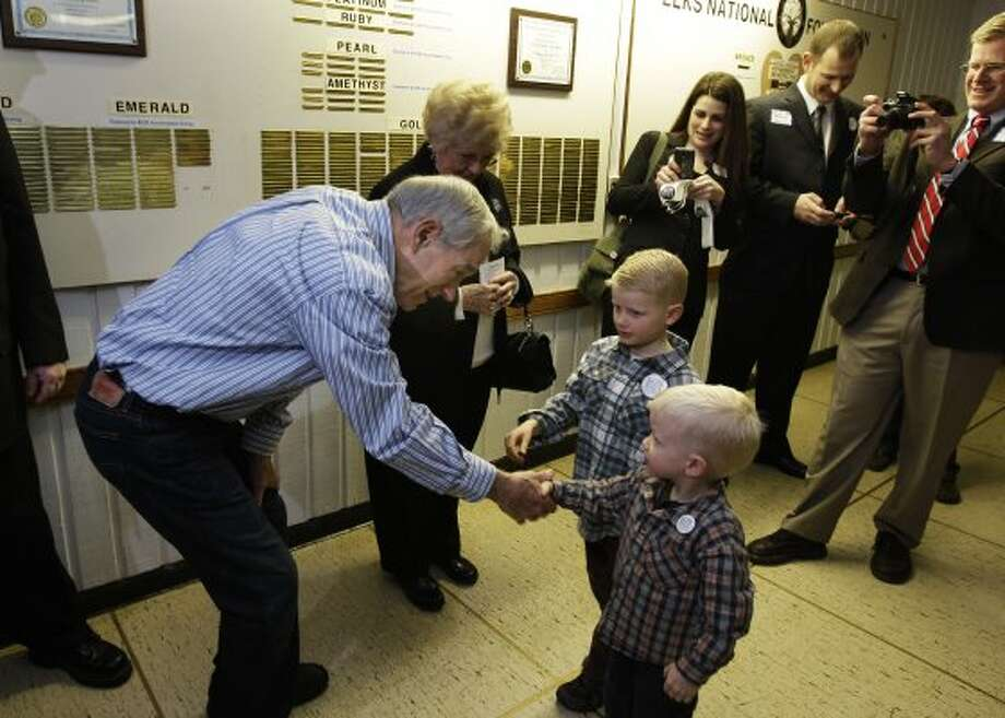 Ron Paul shakes hands with Henry Nichols, 3, and Davis Nichols, 6, as Paul and his wife, Carol, greet people at Washington state caucus meetings, Saturday, March, 3, 2012, in Puyallup, Wash. (Ted S. Warren / The Associated Press)