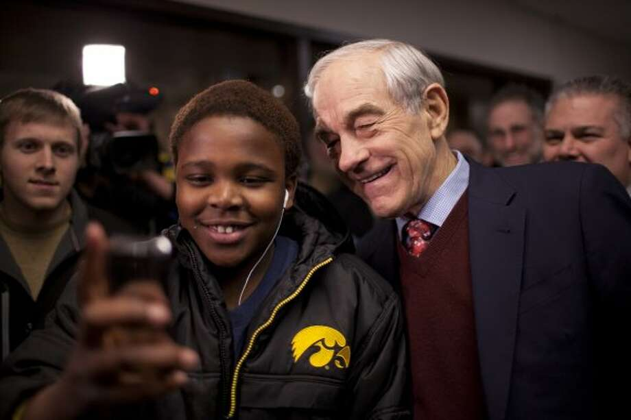 Republican presidential candidate Ron Paul poses for a photo with a boy at Coon Rapids Middle School in Coon Rapids, Minn., Tuesday, Feb. 7, 2012. (Jeff Wheeler / The Associated Press)