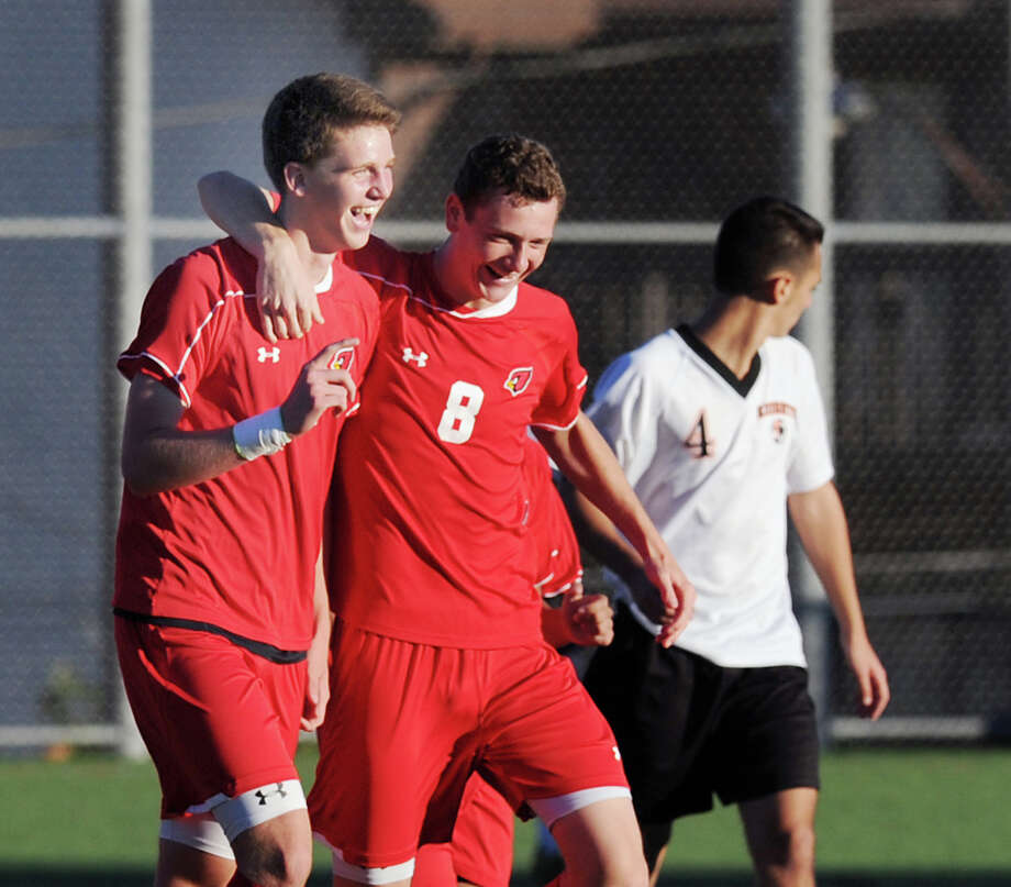 At left, Will Gittings # 4 of Greenwich gets a hug from teammate Jon Palmer # 8 just after Gittings scored on a direct kick putting Greenwich up 2-1 in the second half during the boys high school soccer match between Stamford High School and Greenwich High School at Stamford, Tuesday afternoon, Oct. 16, 2012. Gittings' goal turned out to be the winning goal as Greenwich won, 3-1. Photo: Bob Luckey / Greenwich Time
