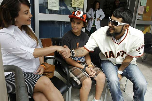 San Francisco Giants' star pitcher, Sergio Romo, (right) greets Sarah Lindberg and sixth grader, Laith Cuyjet, as they wait to receive their Dtap (pertussis booster) vaccines at the Maxine Hall Health Center  in San Francisco, Calif., on Tuesday August 14, 2012.  The San Francisco Immunization Coalition and San Francisco Department of Public Health were joined by community partner the San Francisco Giants today to remind parents and students that vaccines are required to attend school. Photo: Michael Macor, The Chronicle