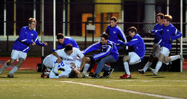 Teammates of Fairfield Ludlowe's #10 Tobias Gimand rush in to celebrate his goal winning shot, during boys soccer action against Staples in Fairfield, Conn. on Tuesday October 16, 2012. Photo: Christian Abraham / Connecticut Post