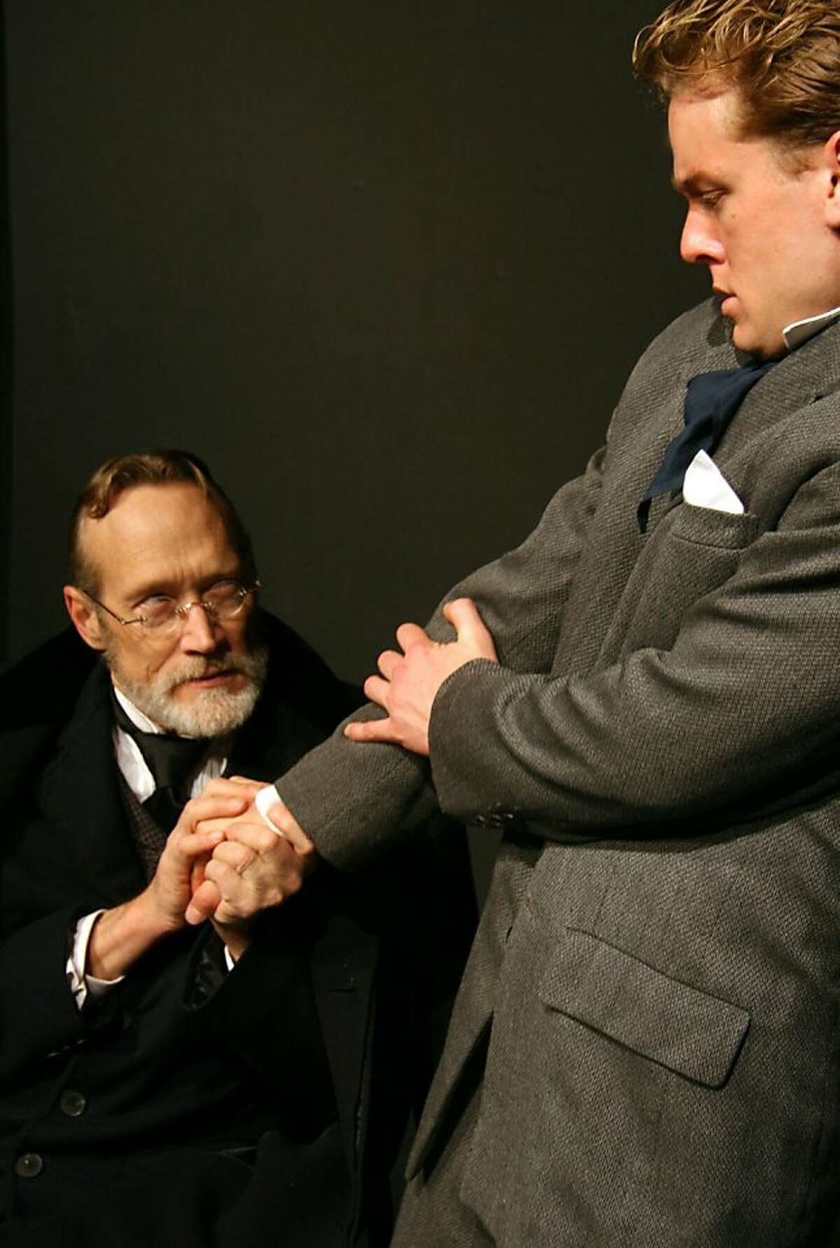 The Old Man (l, James Carpenter) shakes The Student's (r, Carl Holvick-Thomas) hand to seal the bargain in The Ghost Sonata, part of Cutting Ball Theater's Strindberg Cycle: The Chamber Plays in Rep