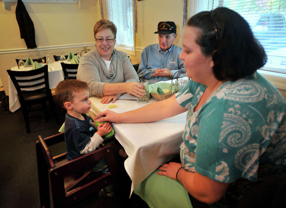 From left, 22-month-old Sage Windebank, Joanne, and Jack Granja and their daughter, Laura Windebank, wait for their meal at The Atlantic Restaurant in Danbury on Tuesday, Oct. 16, 2012. Photo: Jason Rearick / The News-Times