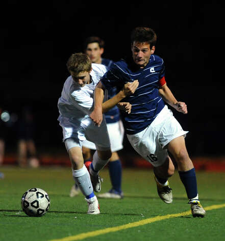 Fairfield Ludlowe's #1 Richie Bellucci, left, and Staples' #16 Joseph Greenwald chase down the ball, during boys soccer action in Fairfield, Conn. on Tuesday October 16, 2012. Photo: Christian Abraham / Connecticut Post