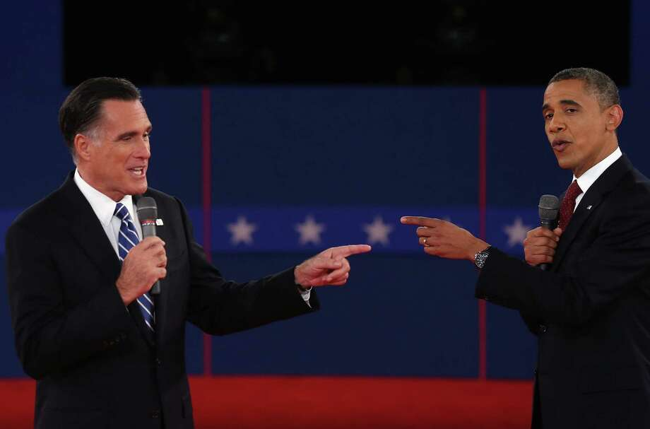 Republican presidential candidate Mitt Romney (L) and U.S. President Barack Obama talk to each other during a town hall style debate at Hofstra University October 16, 2012 in Hempstead, New York. During the second of three presidential debates, the candidates fielded questions from audience members on a wide variety of issues. Photo: Spencer Platt, Getty Images / 2012 Getty Images