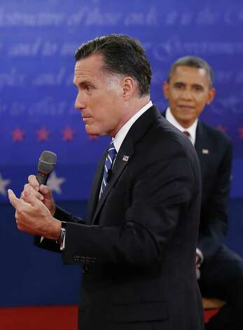 US President Barack Obama listens to Republican presidential candidate Mitt Romney during the second presidential debate on October 16, 2012 at Hofstra University in Hempstead, New York. Obama and Romney faced off Tuesday in a make-or-break debate, vying for command of the presidential race just three weeks from election day. AFP PHOTO / POOLPOOL/AFP/Getty Images Photo: POOL, Pool / AFP