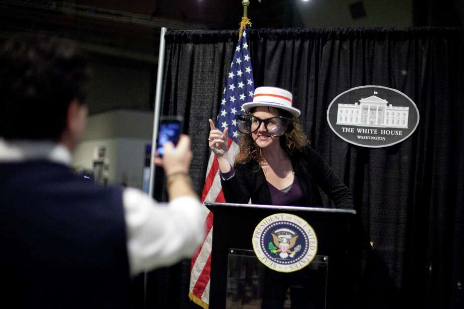 Erica Gustafson strikes a pose at a podium during 'The Next 50' One Stop Ballot Shop debate watch and candidate mingle on Tuesday, October 16, 2012 at the Seattle Center. People gathered in the Center House to watch the debate on a large screen and mingled with candidates and initiative representatives. Photo: JOSHUA TRUJILLO / SEATTLEPI.COM