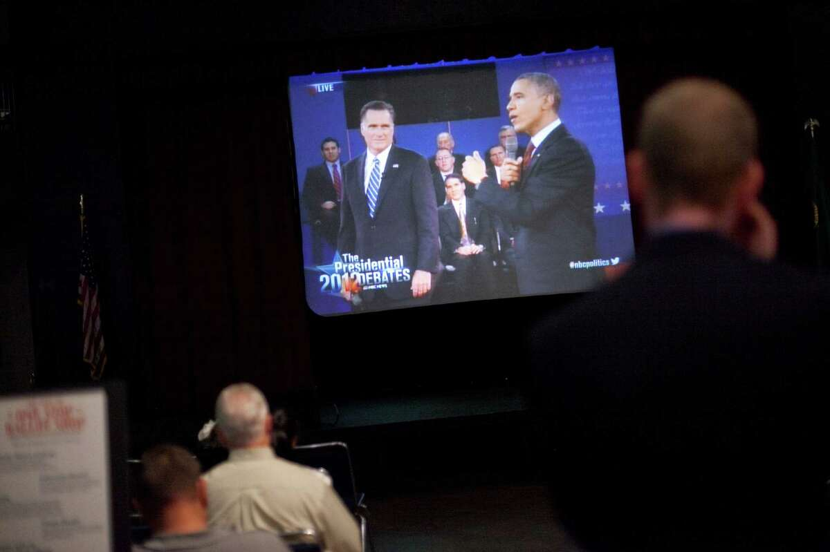 People watch the debate during 'The Next 50' One Stop Ballot Shop debate watch and candidate mingle on Tuesday, October 16, 2012 at the Seattle Center. People gathered in the Center House to watch the debate on a large screen and mingled with candidates and initiative representatives.