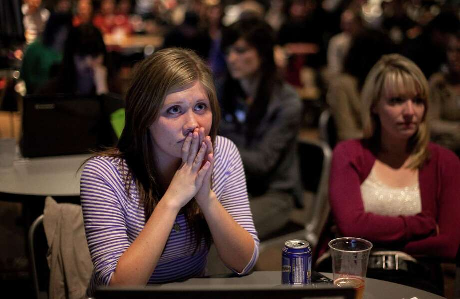 Mallory Smith watches the debate during 'The Next 50' One Stop Ballot Shop debate watch and candidate mingle on Tuesday, October 16, 2012 at the Seattle Center. People gathered in the Center House to watch the debate on a large screen and mingled with candidates and initiative representatives. Photo: JOSHUA TRUJILLO / SEATTLEPI.COM