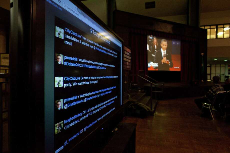 A screen shows Twitter reaction to the debate during 'The Next 50' One Stop Ballot Shop debate watch and candidate mingle on Tuesday, October 16, 2012 at the Seattle Center. People gathered in the Center House to watch the debate on a large screen and mingled with candidates and initiative representatives. Photo: JOSHUA TRUJILLO / SEATTLEPI.COM