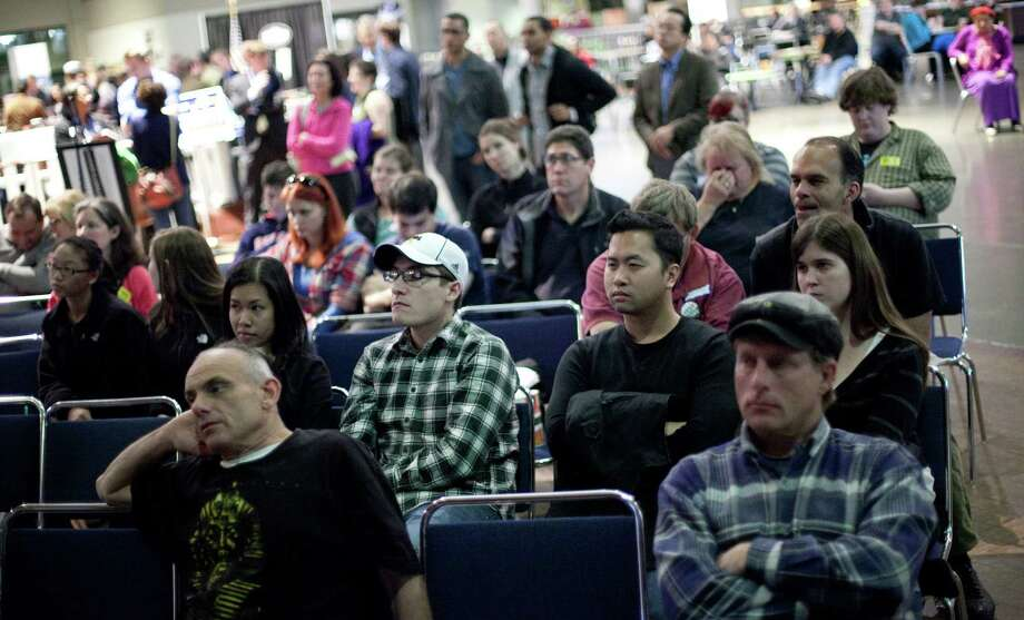 People watch the debate during 'The Next 50' One Stop Ballot Shop debate watch and candidate mingle on Tuesday, October 16, 2012 at the Seattle Center. People gathered in the Center House to watch the debate on a large screen and mingled with candidates and initiative representatives. Photo: JOSHUA TRUJILLO / SEATTLEPI.COM