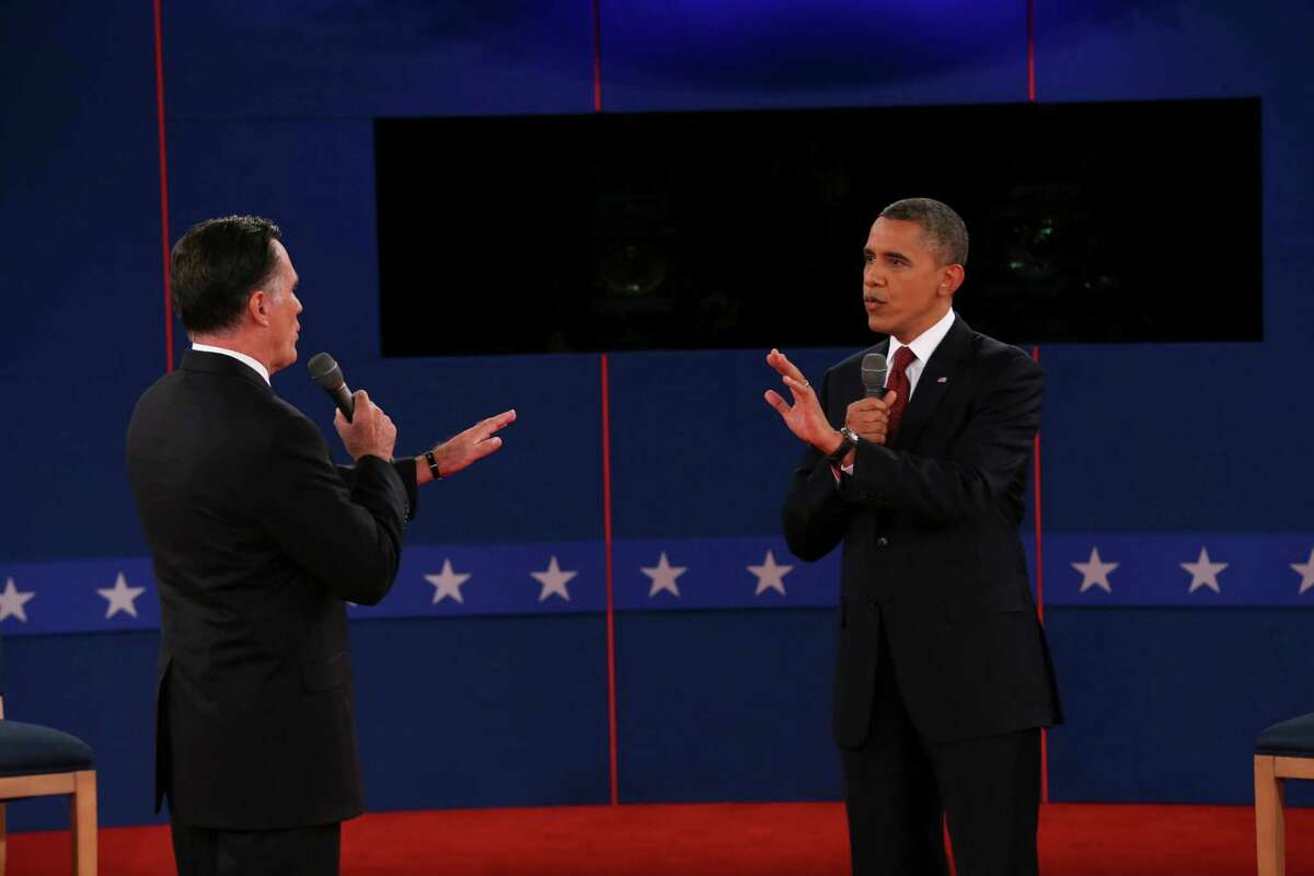 Mitt Romney and President Barack Obama speak to each other while answering a question at a town hall style presidential debate at Hofstra University in Hempstead, N.Y., Oct. 16, 2012. (Doug Mills/The New York Times)