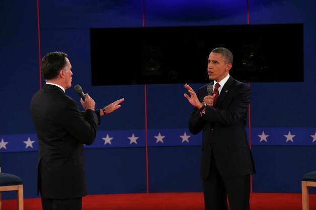 Mitt Romney and President Barack Obama speak to each other while answering a question at a town hall style presidential debate at Hofstra University in Hempstead, N.Y., Oct. 16, 2012.  (Doug Mills/The New York Times) Photo: DOUG MILLS / NYTNS
