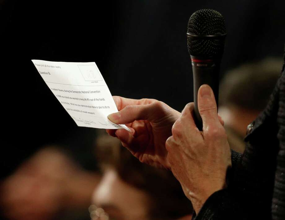 An audience members reads from a printed question during the second presidential debate at Hofstra University, Tuesday, Oct. 16, 2012, in Hempstead, N.Y. (AP Photo/Eric Gay) Photo: Eric Gay