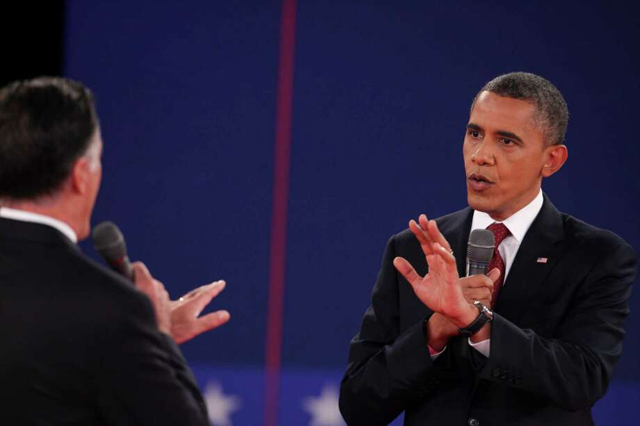 Mitt Romney and President Barack Obama speak to each other while answering a question at a town hall style presidential debate at Hofstra University in Hempstead, N.Y., Oct. 16, 2012.  (Richard Perry/The New York Times) Photo: RICHARD PERRY, NYT / NYTNS
