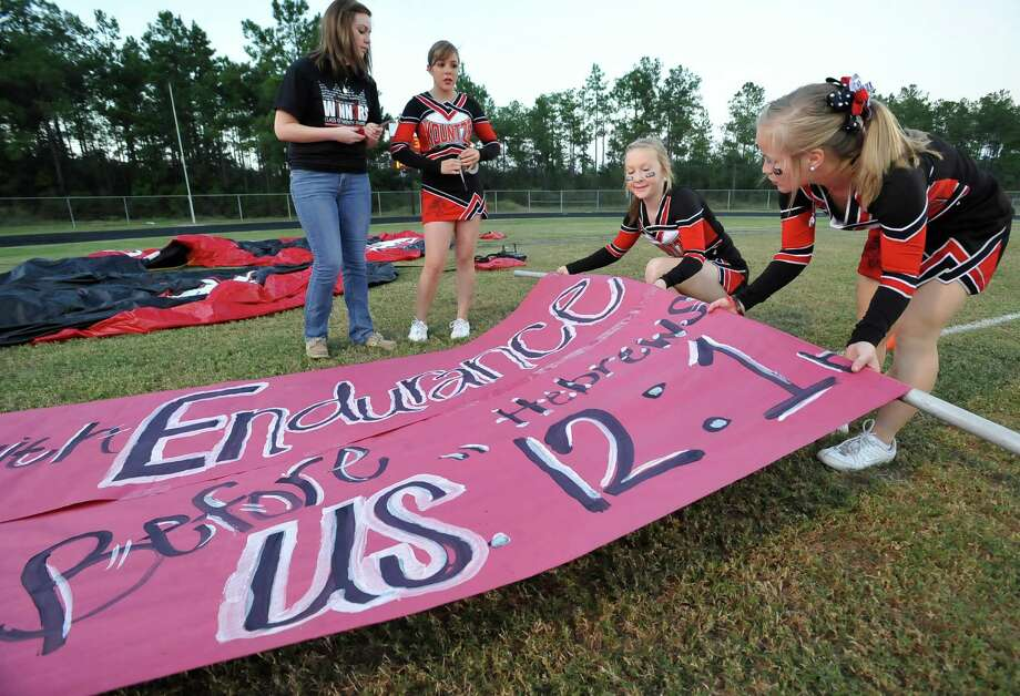 Allison Killough, left, cheerleader sponsor, Megan Tantillo, Morgan Coplen, and Ashton Jennings, right, ready the sign the team will run through.  This was the first home football game in Kountze since the sign controversy started and since the Thursday hearing that determined the cheerleaders could or could not use their faith-based signs.  Dave Ryan/The Enterprise Photo: Dave Ryan