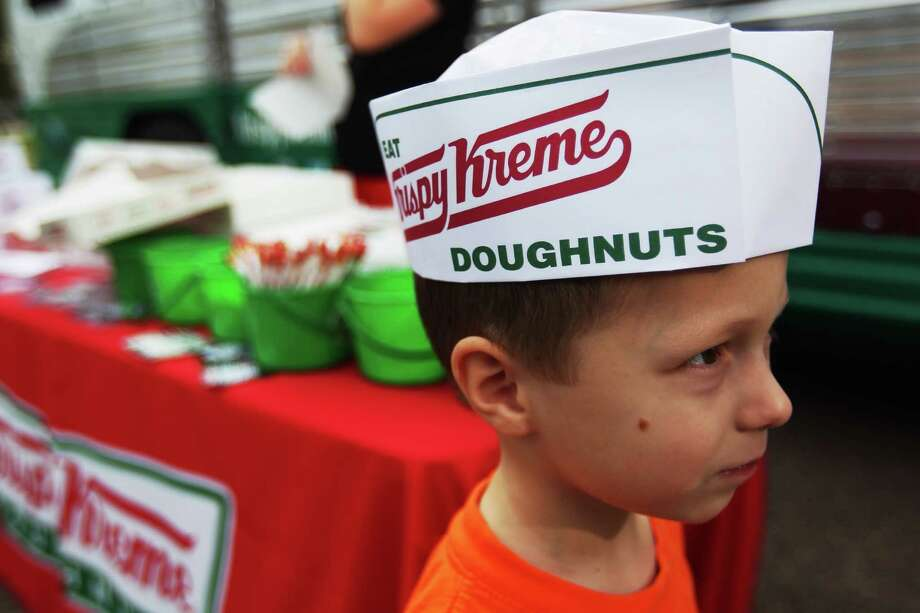 Hudson Getty, 4, wears a Krispy Kreme hat as the Krispy Kreme Cruiser was promoting the doughnut maker's 75th birthday tour by handing out doughnuts in Memorial Park. The bus will be at the Texas Medical Center at Entrance 6 near Texas Children's and St. Luke's hospitals from 1-2 p.m. Then it moves to Fox26 studios at 4261 Southwest Fwy from 3-4 p.m. Oct. 17, 2012. / Johnny Hanson / Houston Chronicle Photo: .