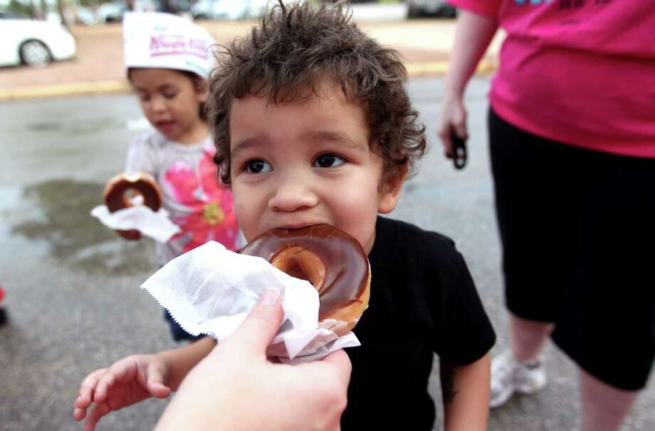 SirCalvin Cooper, 2, munches on a chocolate doughnut as the Krispy