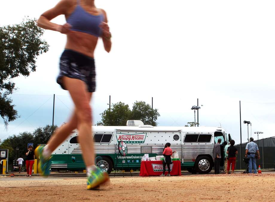 A runner jogs past the Krispy Kreme Cruiser at Memorial Park Tuesday, Oct. 17, 2012. The doughnut maker is promoting its 75th birthday tour with free doughnuts. Catch them at the Texas Medical Center at Entrance 6 from 1-2 p.m. Then  it moves to Fox26 studios at 4261 Southwest Fwy from 3-4 p.m. / Johnny Hanson / Houston Chronicle Photo: .