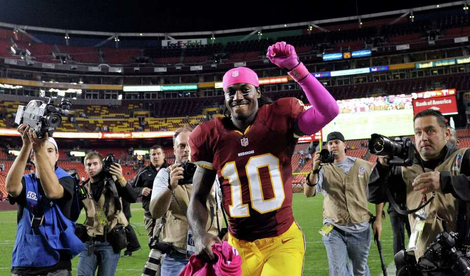 Washington Redskins quarterback Robert Griffin III runs off the field after the an NFL football game between the Redskins and Minnesota Vikings Sunday, Oct. 14, 2012, in Landover, Md. The Redskins defeated the Vikings 38-26.  (AP Photo/Cliff Owen) Photo: Cliff Owen, Associated Press / FR170079 AP