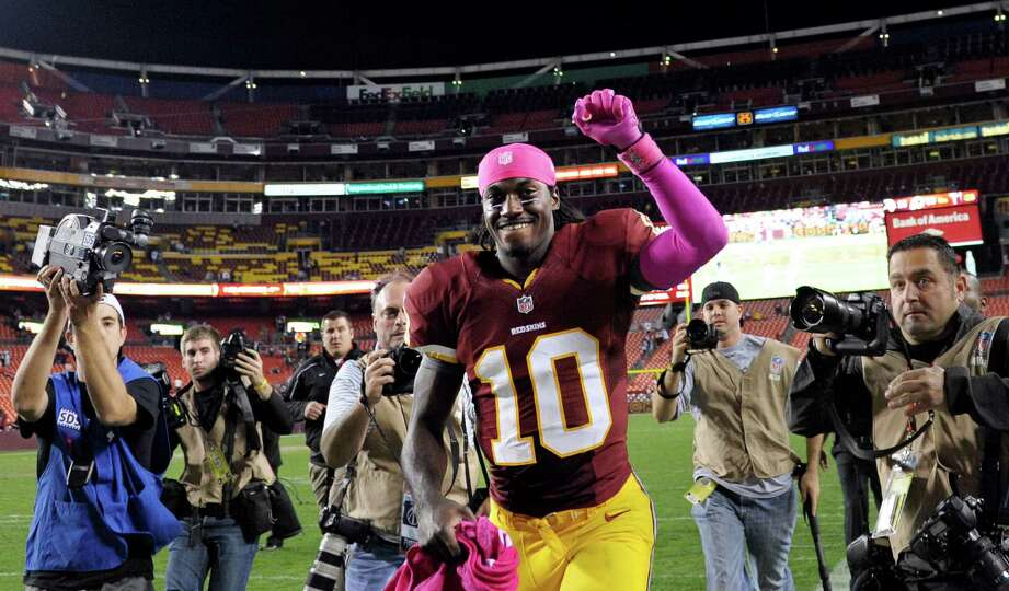 Washington Redskins quarterback Robert Griffin III runs off the field after the an NFL football game