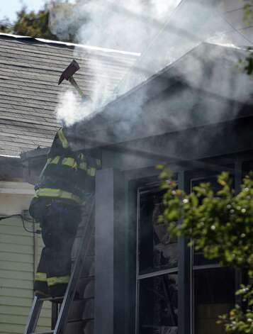 Albany Fire Department personnel work a fire at 20 Benson St. in Albany, N.Y. Oct 17, 2012. A child rescued from the building was taken to a burn unit in Boston by helicopter, according to Chief Robert Forezzi of the Albany Fire Department. (Skip Dickstein/Times Union) Photo: SKIP DICKSTEIN