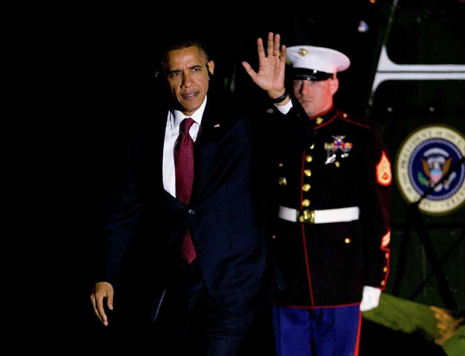 President Barack Obama waves as he arrives the White House in Washington early Wednesday, Oct. 17, 2012, following the second presidential debate with Republican presidential candidate Mitt Romney, at Hofstra University in Hempstead, N.Y.  (AP Photo/Manuel Balce Ceneta) Photo: Manuel Balce Ceneta, Associated Press / AP