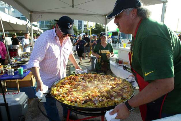 Alex Richards, left, and his brother Arnaldo Richards make paella during a tailgate party outside Reliant Stadium before the Houston Texans and Green Bay Packers Sunday Night Football game on Sunday, Oct. 14, 2012, in Houston. ( Brett Coomer / Houston Chronicle ) Photo: Brett Coomer / © 2012  Houston Chronicle