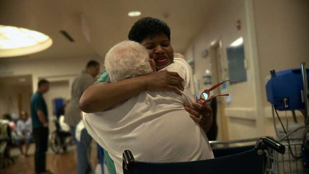 Certified Nurse Assistant Cynthia Y. Johnson embraces a patient in The Waiting Room. Photo: International Film Circuit, Inc.