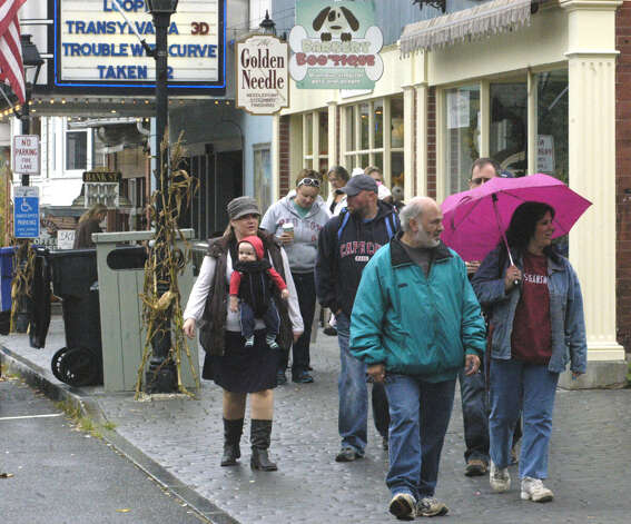 Linda Calabrese of New Milford protects herself from a brief shower as she strolls Bank Street with her brother, Tony Calabrese, during the Greater New Milford Chamber of Commerce's Harvest Festival, Oct. 7, 2012 in the New Milford village center. Photo: Norm Cummings