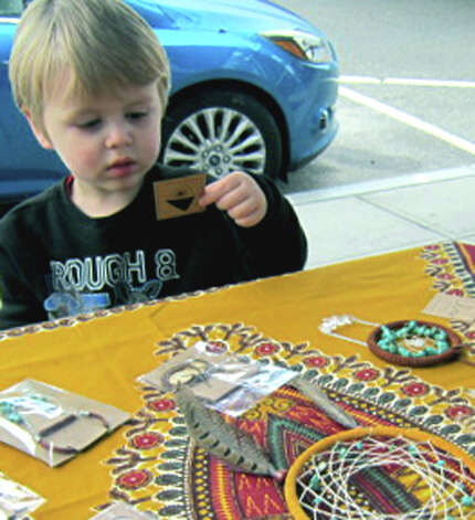 Young Liam Curley, 3, of New Milford is fascinated by the variety of handmade items created by Rebekah Sutter and available for purchase at a sidewalk stand in front of The Sweet Spot, where Rebekah works, during the Greater New Milford Chamber of Commerce's Harvest Festival, Oct. 7, 2012 in the New Milford village center. Photo: Norm Cummings