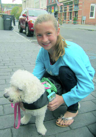 Hannah Lasky, 11, of New Milford and her longtime canine friend, Caly, were among the many disappointed to learn the Barkery Boo'tique's popular dog parade had been postponed Oct. 7, but relieve to know it would be held at a date to be determined. Photo: Norm Cummings