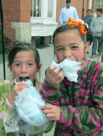 Avery Trach, 7, and big sister Cadence, 10, of New Milford are shy about wolfing down delicious cotton candy courtesy of Daniel's Dining Car during the Greater New Milford Chamber of Commerce's Harvest Festival, Photo: Norm Cummings