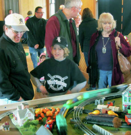 A display of miniature trains presented by New Milford resident AdamWeaverat the railroad station proves an attraction during the Greater New Milford Chamber of Commerce's Harvest Festival for Ryan Thibodeau, 11, and his dad, Michael Thibodeau, as welll as many others. Oct. 7, 2012 Photo: Norm Cummings